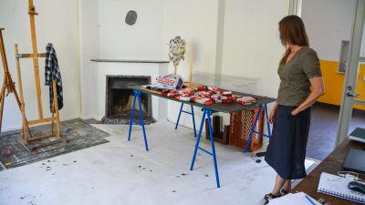 En kvinna står i ett rum som fungerar som en konstnärsateljé.