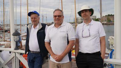 Tre män står brevid varandra framför en hamn med segelbåtar.