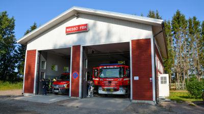 Wessö FBK stationen utifrån. På bilden syns ett ett hus med två öppningar där det står två brandbilar.