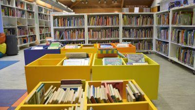 Hyllor med lådor och böcker i ett bibliotek.