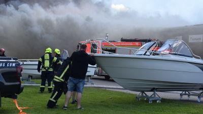 Räddningverket och privatpersoner tömmer båtar från en brinnande byggnad.