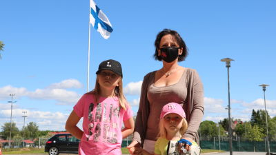 En kvinna med två barn. I bakgrunden svajar Finlands flagga.