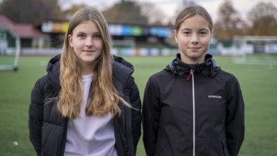 Alina Johansson och Emelie Enberg står utomhus på en konstgräsplan och tittar in i kameran.