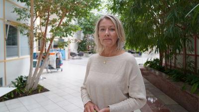 Mona Burlin ser in i kameran. I bakgrunden en korridor med växter.