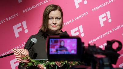 Katju Aro på valvaka med kamera i förgrunden och partireklam i bakgrunden.