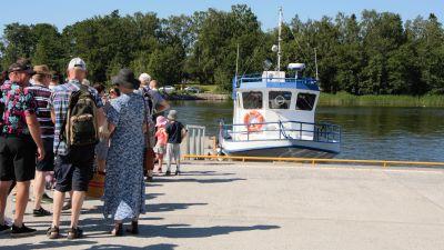 Flera människor som står i kö för att gå ombord på en skärgårdskryssning.