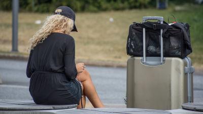 Kvinna sitter och tittar på sin telefon med kappsäck bredvid sig.