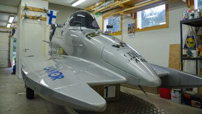 En grå formel 4 racerbåt av katamarantyp står i ett garage.