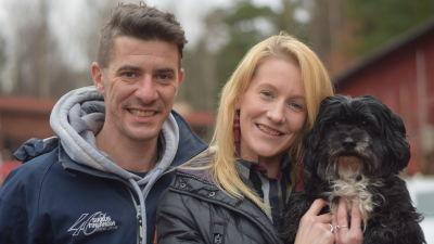 En leende man och kvinna och en hund.