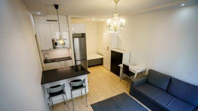 Rum med vita väggar, ljust trägolv, kök och möbler. En etta som är till salu.