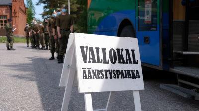 """en vit skylt där det står """"vallokal"""", i bakgrunden står beväringar och köar för att få rösta."""