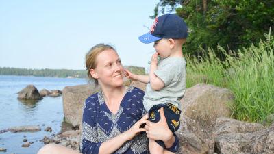 Sandra Söderholm sitter på en sten på en strandkant och håller om sin son Kevin Blomqvist.