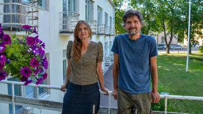 En kvinna och en man står och lutar mot ett räcke på en balkong.