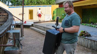 En man bär en högtalare framför en scen.