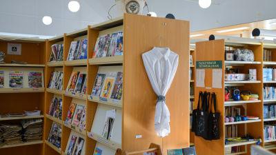 En vit skjorta hänger på en galge på en bokhylla i ett bilbiotek. Skjortan har en metallkedja fastspänd runt sig.