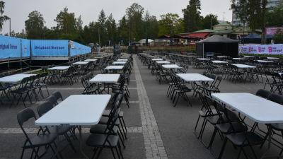 Bord och stolar på ett festivalområde.