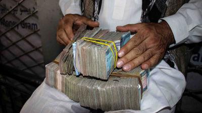En man med stora sedelbuntar i famnen i Kabul, Afghanistan.