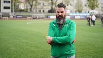 en medelåldersman i mörkt hår och skägg som har på sig en grön träningsdräkt med Ekenäs IF-logo.