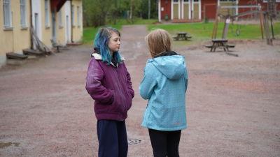 Två skolbarn som står på skolgården och talar