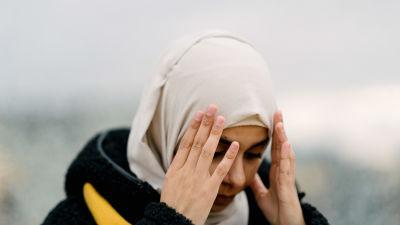 Kvinna i svart rock och vit hijab. En hijab är ett tygstycke som täcker bärarens hår och hals.