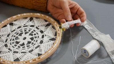 Hand syr fast spetsband på en tavla gjord med virkad duk och sybåge