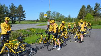 En grupp cyklister i gula dräkter har tagit paus vid en busshållplats.