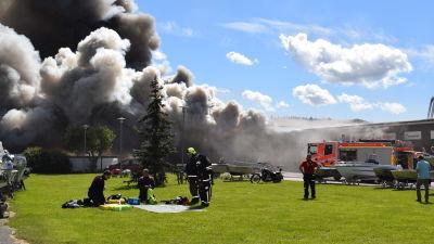 brandmän framför brinnande affärshus