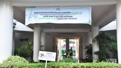 Många bostadshus är försedda med banderoller som uppmanar invånarna att låta vaccinera sig. Också i Malaysia ställer sig en del människor skeptiskt till vaccin.