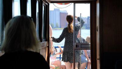 En ung kvinna står i en båt och tittar ut över Vasa stad.