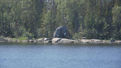 En stor sten med ett vitt kors på.