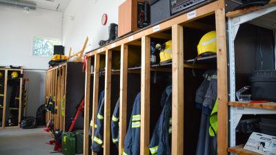 Brandmansutstyrsel hänger på rad i knaggar.