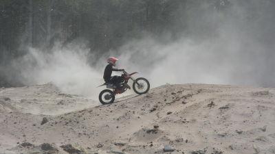 En motocrossförare åker på sand.
