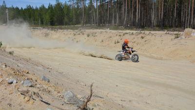 En motocrossförare kör på en sandbana.