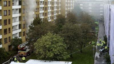 Bild på flervåningshus där det brinner. På marken står det flera brandmän.