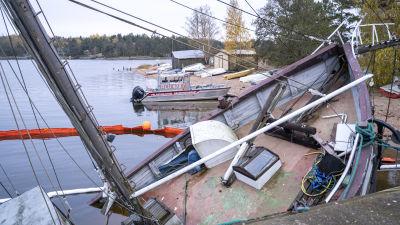 En sjunkande trålare ligger förtöjd vid en kaj. I bakgrunden syns en räddningsbåt och oljabommar som avgränsar området kring trålaren.