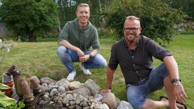 Två män som sitter i en trädgård bredvid en fontän som är byggd av ett gammalt stanklås.