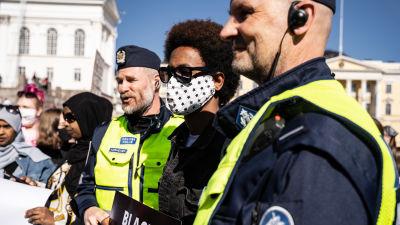 En demonstrant står mellan två poliser.