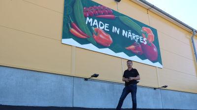 En man står intill en gul vägg. På väggen finns en stor skylt med texten Made in Närpes.