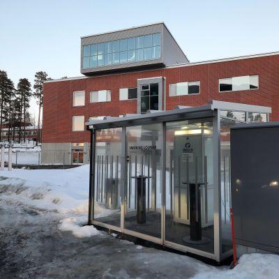 Lasiseinäinen tupakointikoppi Keski-Suomen keskussairaalan pysäköintialueen reunassa
