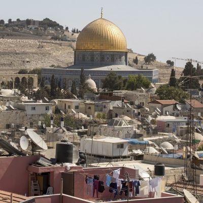 Kultakupolinen moskeija, takana kukkulalla hautausmaa, edessä asuintaloja satelliittiantenneineen ja kuivumaan ripustettuine pyykkeineen.