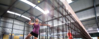 Två personer spelar padeltennis. I förgrunden en kvinna, i bakgrunden en man.