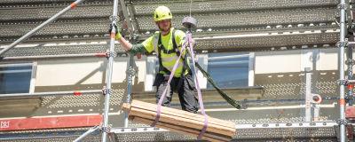 En arbetare tar emot brädor som hissas upp till honom på en byggställning.
