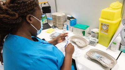 Sairaanhoitaja Diana Boateng valmistelee koronarokote Helsingin Messukeskuksessa.