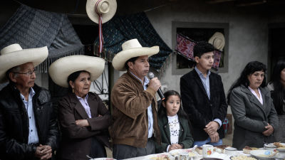 Presidentknidaten Pedro Castillo står  bakom ett bord och talar i en mikrofon. Bredvid honom står en rad män och kvinnor och ett barn.