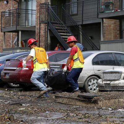 Kaksi kypäräpäistä miestä suojaliiveissä kantaa jätesäkkiä, taustalla likaantuneita autoja.