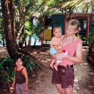 Nuori Anni Valtonen pienten poikiensa kanssa nicaragualaisen trooppisen vehreyden keskellä, taustalla puuvaja ja meri.