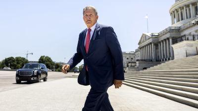 Joe Manchin lämnar Capitolium i soligt väder.