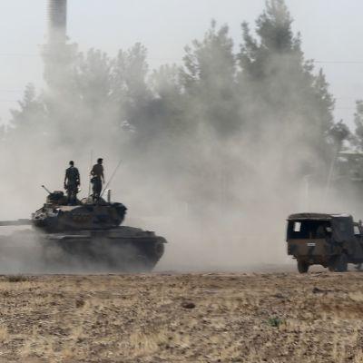 Panssarivaunu koko kuvassa pellolla. Päällä seisoo kaksi miestä. Maa pöllyää. Vieressä ajaa jeeppi eri suuntaan.