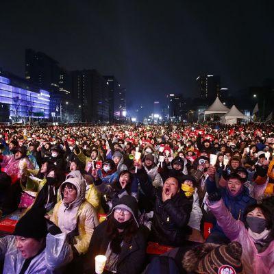 Kuvassa mielenosoittajia Soulin pääkadulla. Mielenosoittajilla kylttejä ja he vaativat presidenttiä eroamaan.