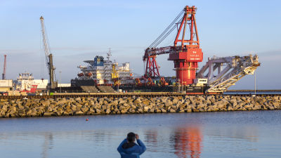 Ett stort fartyg ligger i hamn bakom en vågbrytare av sten.